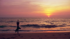 Young beautiful woman doing yoga on beach at sunset - tree pose slow motion Stock Footage