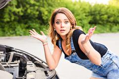 Feeling confusion. Portrait of embarrassed young woman with broken car Stock Photos