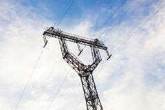 the pylons of a power line with blue sky - stock photo