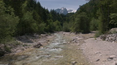 Aerial - Flight above river through a forest with snowy mountains in the backgro Stock Footage