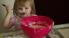 Little girl eating dough in the kitchen Stock Footage