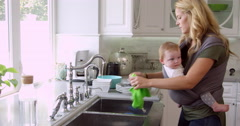 Busy Mother With Baby In Sling At Home Shot On R3D - stock footage