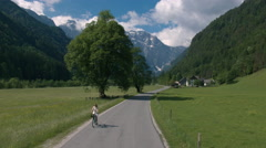 Aerial - Young woman in white dress riding bicycle on road through the valley Stock Footage