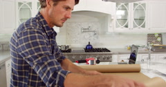 Man At Home Wrapping Package For Mailing Shot On R3D - stock footage