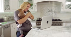 Busy Mother With Baby In Sling At Home Shot On R3D Stock Footage