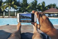 Low section of man photographing swimming pool in tourist resort - stock photo