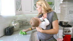 Busy Mother With Baby In Sling At Home, Slow Motion Stock Footage