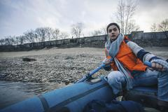 Teenage girl wearing life jacket while rafting in lake Stock Photos