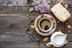 Rustic wooden background with cup of coffee, milk, bun with marzipan and lila Stock Photos