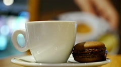 Cup of coffee with brown macaron in an indoor café Stock Footage