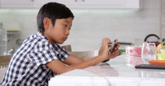 Young Asian Boy Playing Game On Mobile Device Shot On R3D Stock Footage