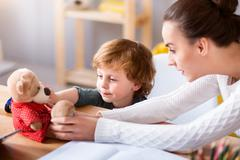 Woman and child sitting at the table Stock Photos