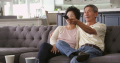 Senior Asian Couple At Home On Sofa Watching TV Shot On R3D Stock Footage