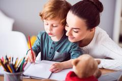 Mother looking at child drawing a picture Stock Photos