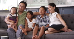 Family Sitting On Sofa At Home Watching TV Shot On R3D - stock footage