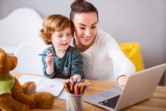 Mother and child looking at laptop Stock Photos