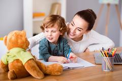 Mother and son looking at teddy bear Stock Photos
