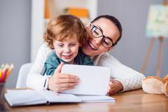 Mother and child looking at tablet - stock photo