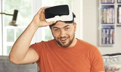 Young man wearing virtual reality googles. His livingroom transforms into VR - stock photo