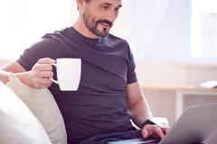 Man having drink and working on computer - stock photo