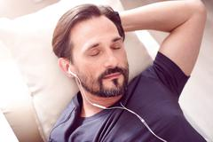 Bearded man sleeping with earphones Stock Photos
