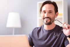 Man holding glasses and looking at camera - stock photo