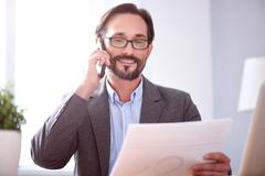Man looking at paper while having conversation Stock Photos