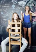 back to school after summer vacations, two teen real girls in classroom with - stock photo
