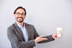 Man pointing at cup of coffee - stock photo