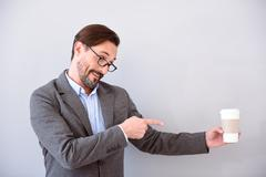 Man pointing and looking at cup - stock photo