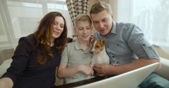 A friendly happy family with a dog the Jack Russell Terrier talking to relatives Stock Footage