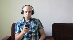 A man sits in a chair and listening to music on headphones. Sings songs. Stock Footage