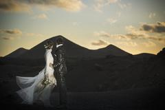 Full length side view of loving bridge and groom standing on volcanic landscape Stock Photos