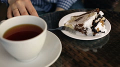 Woman eating cake in restaurant with cup of tea - stock footage