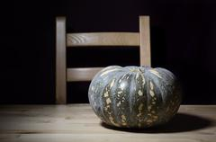 Solitary pumpkin on rustic table with chair. Stock Photos