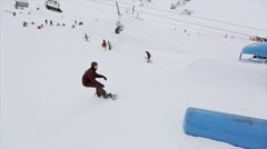 Snowboarder jump on springboard in snowy mountain. Stunts. Contest. Competition Stock Footage