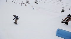 Snowboarder jump on springboard, turn over in snowy mountain. Stunts. Contest - stock footage