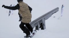 Snowboarder jump on iron trail, but fail in snowy mountain. Stunts. Contest - stock footage