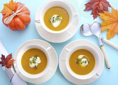 Thanksgiving table setting with pumpkin soup. - stock photo