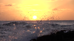 SLOW MOTION CLOSE UP: Ocean waves splashing into rocky shore at golden sunset Stock Footage
