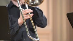 Trombonist playing the trombone, close-up, blurred defocused background Stock Footage