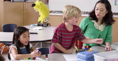 Teacher sits with young kids in school class, shot on R3D Stock Footage
