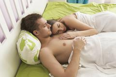 High angle view of shirtless couple sleeping on bed Stock Photos