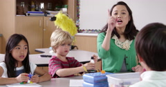 Teacher sits with young kids using blocks, shot on R3D Stock Footage