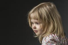 Side view of girl crying against black background Stock Photos