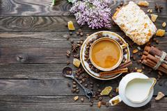Rustic wooden background with cup of coffee, milk, marzipan bun and lilac flo Stock Photos
