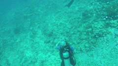 UNDERWATER: View from above of woman diving in pacific waters looking coral reef Stock Footage