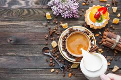 Rustic wooden background with cup of coffee, milk, fruit tart and lilac flowe Stock Photos