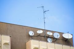 Low angle view of antennas and satellite dishes on building against sky Stock Photos