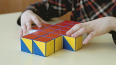 A boy collecting a pattern using colored cubes Stock Footage